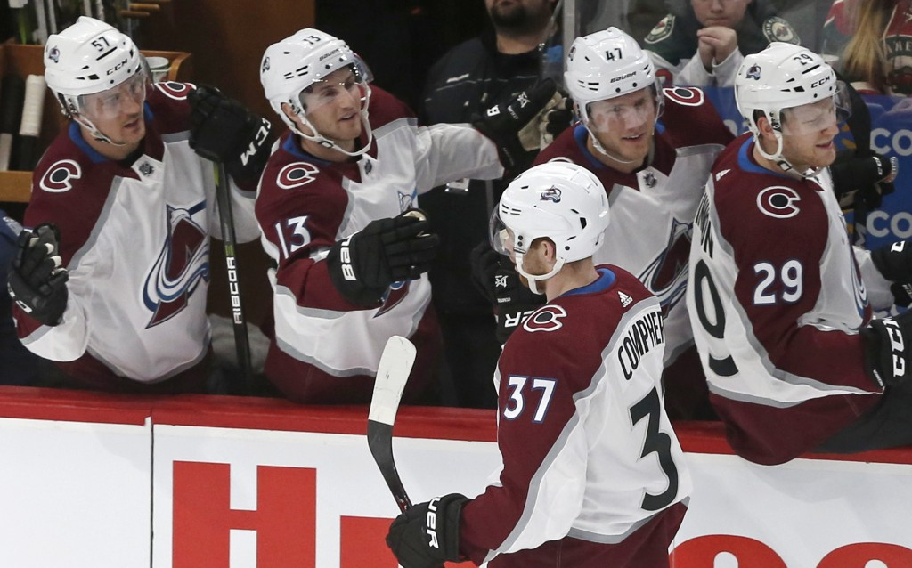 Colorado Avalanche's J.T. Compher (37) is congratulated by teammates after he scored against Minnesota Wild goalie Devan Dubnyk in the first period of