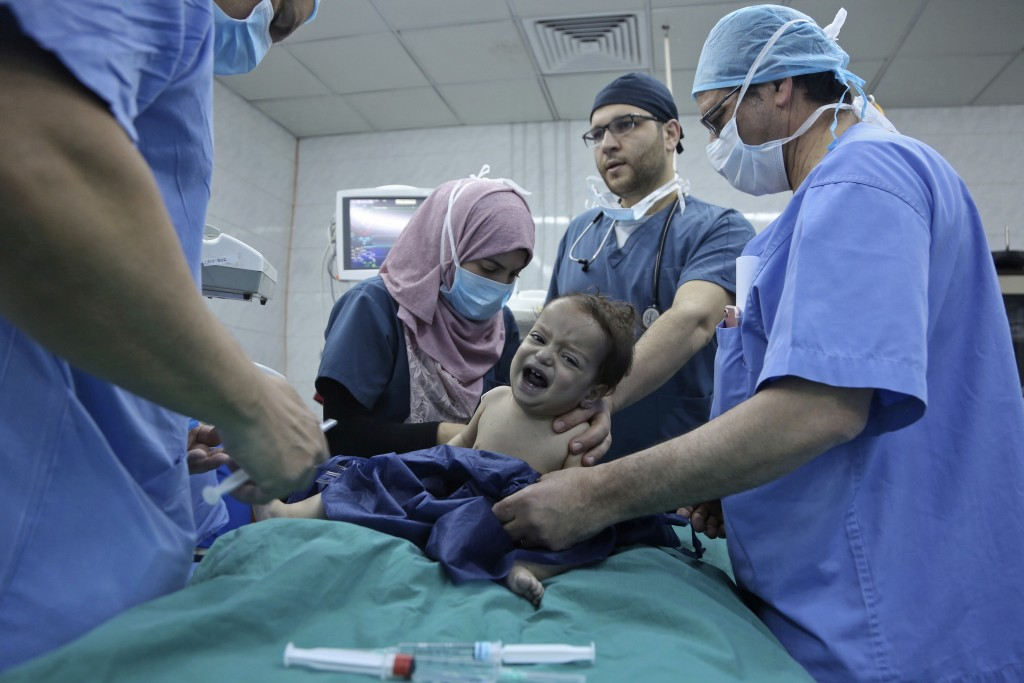 In this March 5, 2018 photo, one-year-old Syrian refugee Eman Zatima is prepared by medical staff for surgery, at a hospital in Amman, Jordan. Eman, w