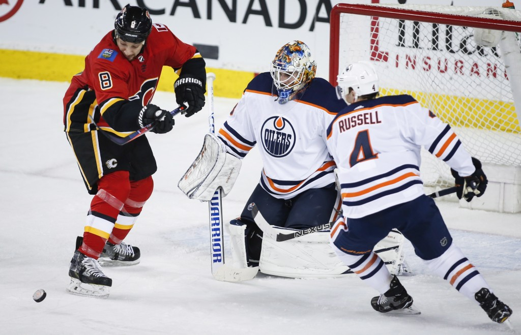 Edmonton Oilers goaltender Cam Talbot (33) and defenseman Kris Russell (4) look on as Calgary Flames right wing Chris Stewart (8) tries for a rebound