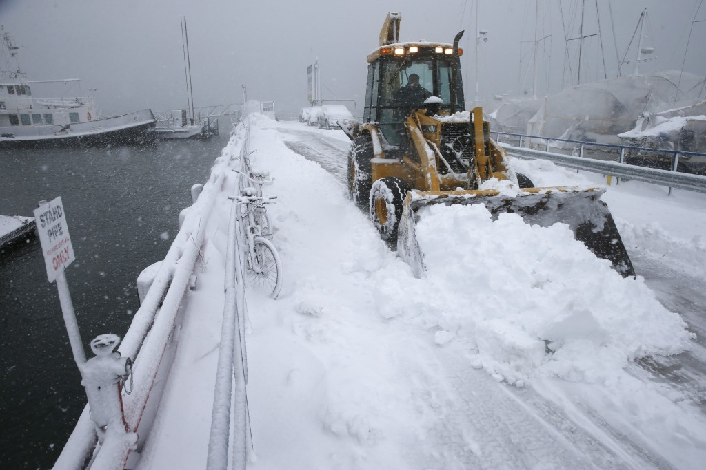 A front end loader clears the pier at the Boston Harbor Shipyard and Marina in Boston, Tuesday, March 13, 2018. Boston finds itself in the bullseye of