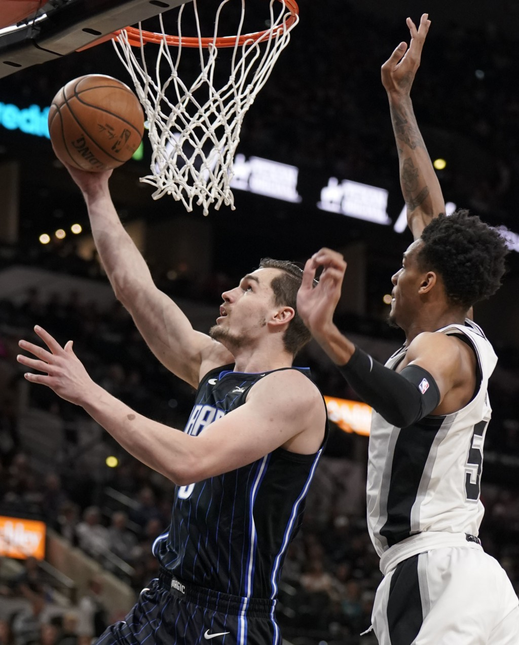 Orlando Magic's Mario Hezonja, left, shoots against San Antonio Spurs' Dejounte Murray during the first half of an NBA basketball game, Tuesday, March