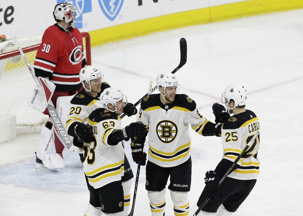 Boston Bruins' David Pastrnak (88), of the Czech Republic, is congratulated by Riley Nash (20), Brad Marchand (63) and Brandon Carlo (25) following Pa
