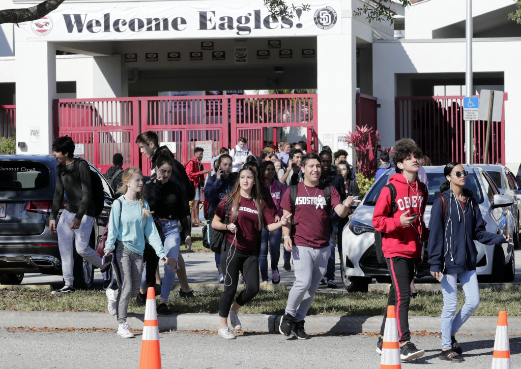 Students walk out of Marjory Stoneman Douglas High School, as part of a nationwide protest against gun violence, Wednesday, March 14, 2018, in Parklan