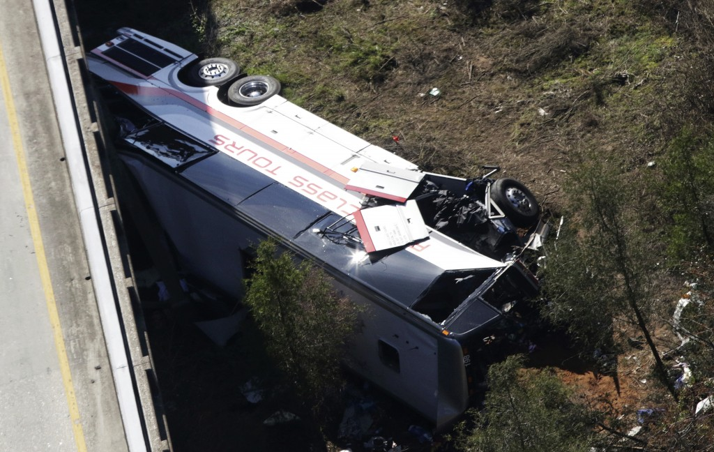 A charter bus sits in a ravine after a deadly crash on Tuesday, March 13, 2018, in Loxley, Ala. The bus carrying Texas high school band members home f