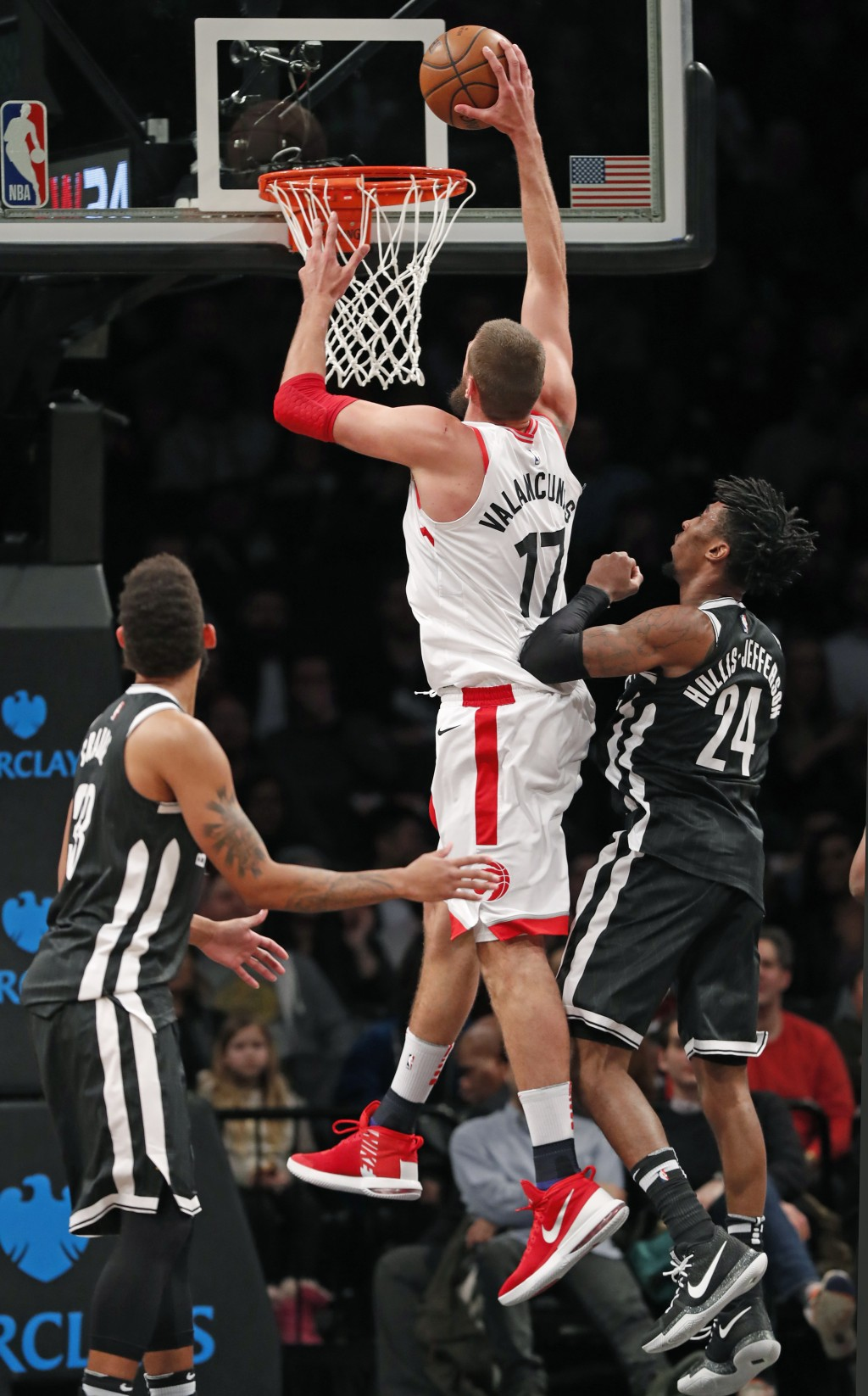 Toronto Raptors center Jonas Valanciunas (17) dunks over Brooklyn Nets forward Rondae Hollis-Jefferson (24) during the second half of an NBA basketbal