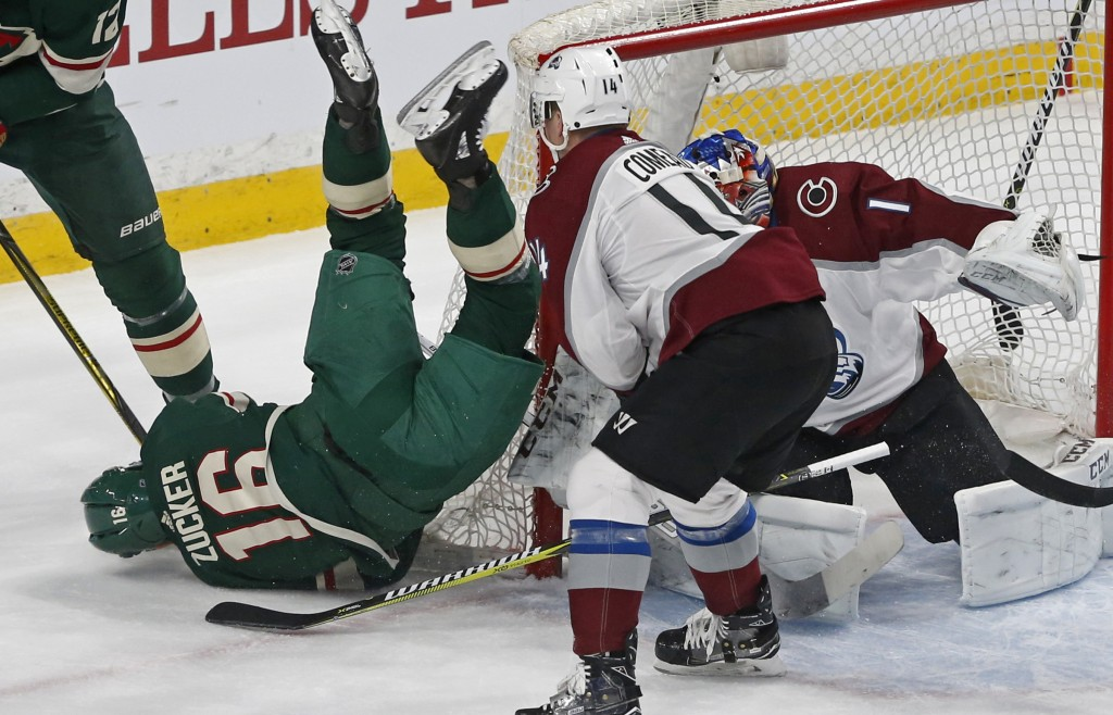 Minnesota Wild's Jason Zucker, left, tumbles to the ice over Colorado Avalanche goalie Semyon Varlamov, of Russia, in the first period of an NHL hocke