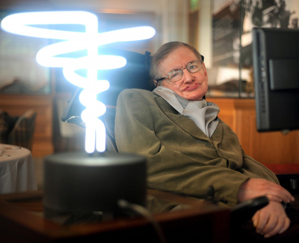 In this Feb. 25, 2012 photo, Professor Stephen Hawking poses beside a lamp titled 'black hole light' by inventor Mark Champkins, presented to him duri