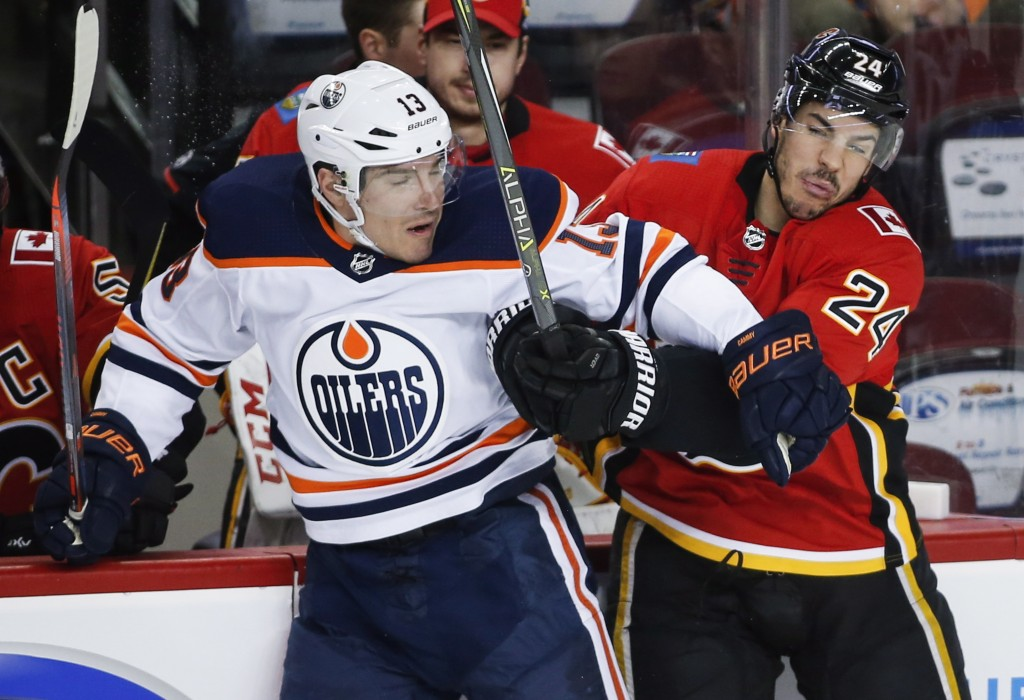 Edmonton Oilers left wing Michael Cammalleri (13) is checked by Calgary Flames defenseman Travis Hamonic (24) during the first period of an NHL hockey