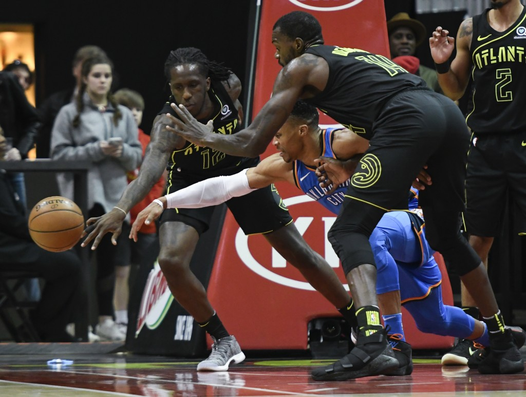 Atlanta Hawks forward Taurean Prince, left, Oklahoma City Thunder guard Russell Westbrook and center Dewayne Dedmon, right, vie for a loose ball durin