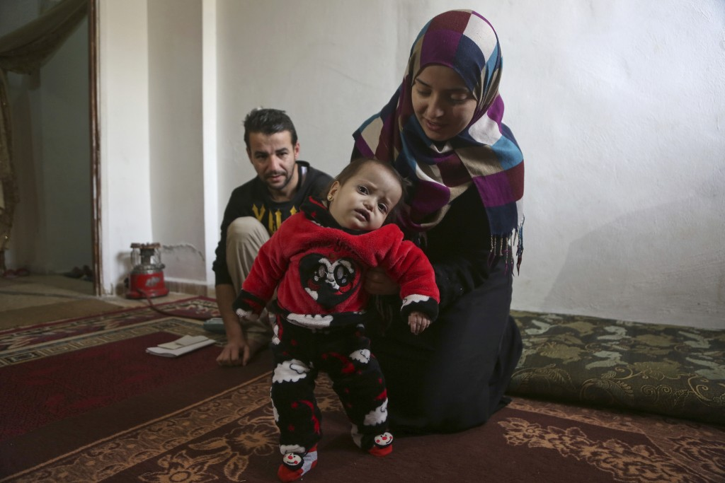 In this February 22, 2018 photo, Syrian refugees Alaa Zatima and his wife Sara al-Matoura, pose with their daughter, one-year-old Eman, in their home