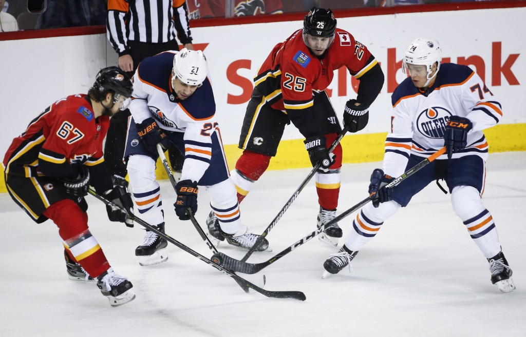 Edmonton Oilers left wing Milan Lucic (27) and defenseman Ethan Bear (74) battle for the puck with Calgary Flames right wing Michael Frolik (67), from