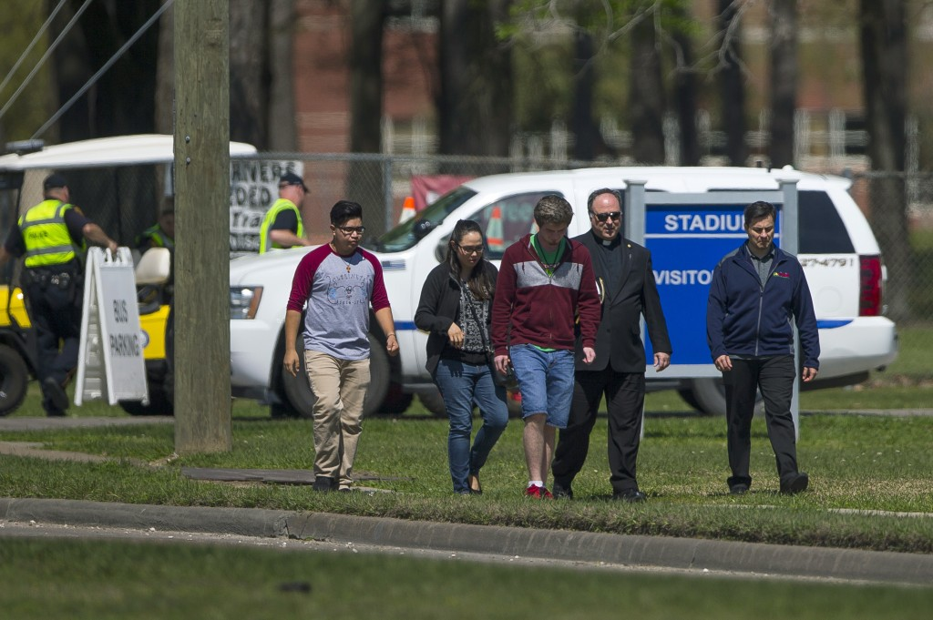 A group of people who said they were on campus to offer support to those effected by a bus crash earlier in the day in Alabama walk down Sheldon Road