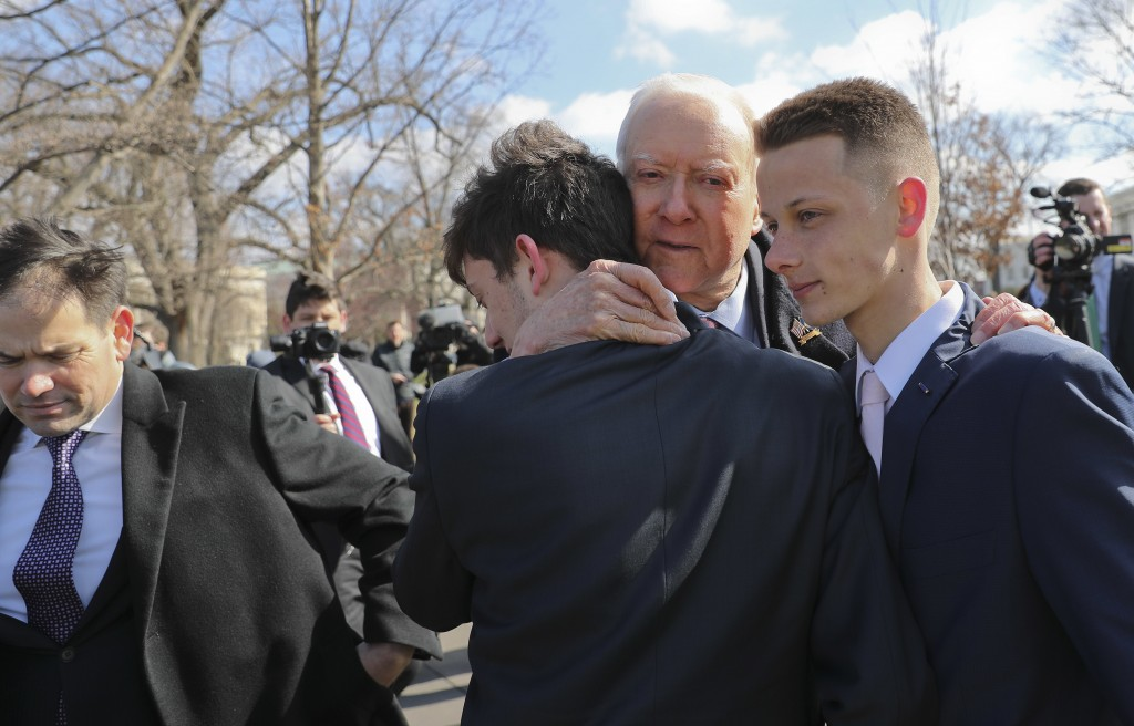 Sen. Orrin Hatch, R-Utah, center, hugs Kyle Kashuv, 16, and Patrick Petty, 17, both from Parkland, Fla., following a news conference on Capitol Hill i