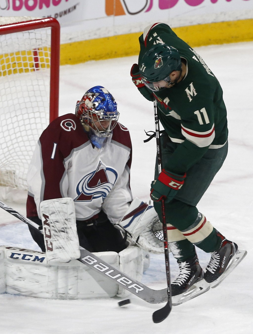 Minnesota Wild's Zach Parise, right, attempts to score as Colorado Avalanche goalie Semyon Varlamov, of Russia, blocks the shot in the first period of