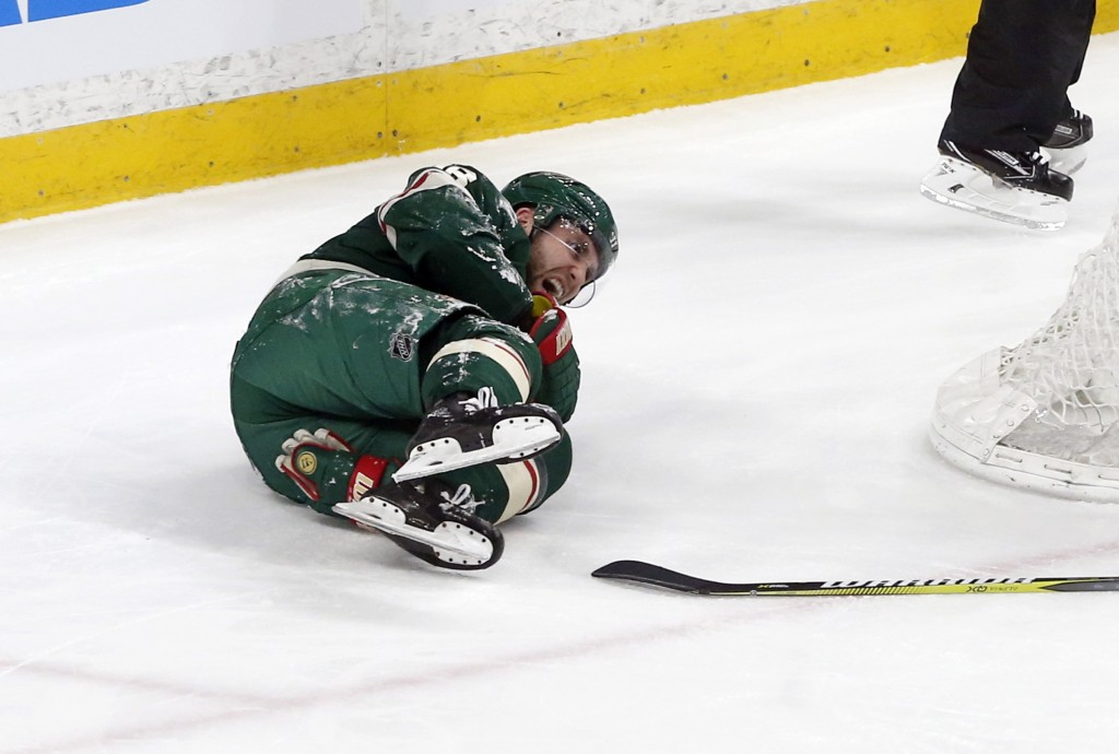 Minnesota Wild's Jason Zucker grimaces after he tumbled to the ice over Colorado Avalanche goalie Semyon Varlamov, of Russia, in the first period of a