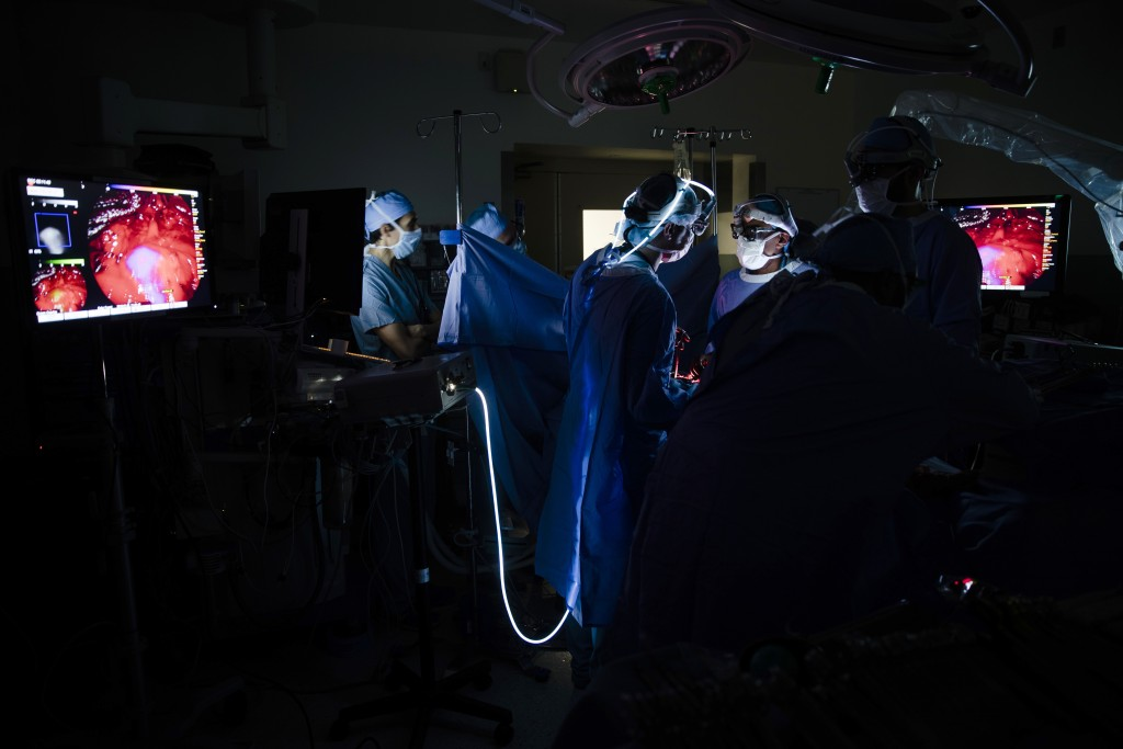 Dr. Sunil Singhal, center right, views a monitor to look at a tumor in his patient, made visible with the use of a special camera and fluorescent dye