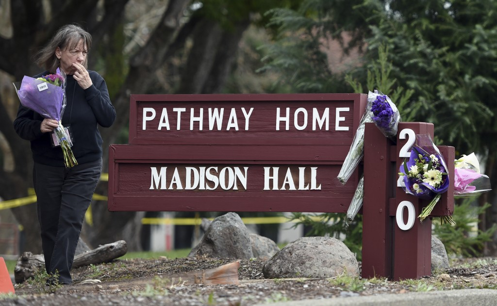 FILE - In this March 10, 2018 file photo, a woman who declined to give her name reacts while placing flowers at a sign outside the Pathway Home in You