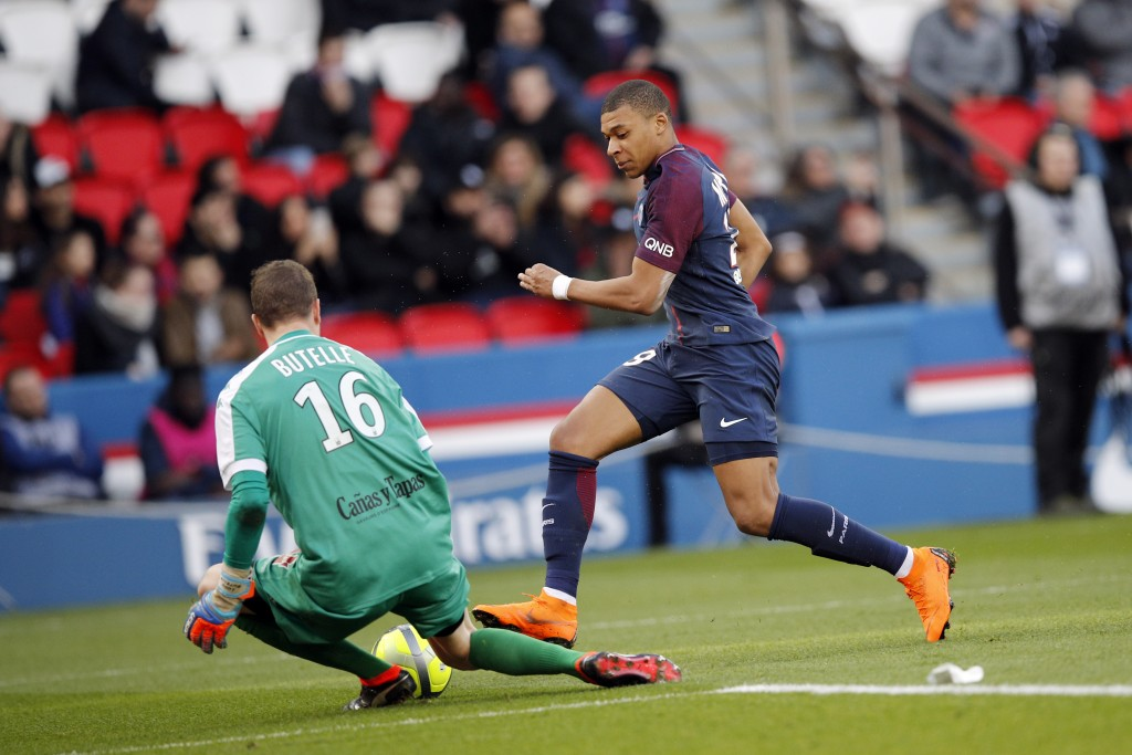 PSG's Kylian Mbappe, right, challenges with Angers' Ludovic Butelle during the French League One soccer match between Paris Saint-Germain and Angers a