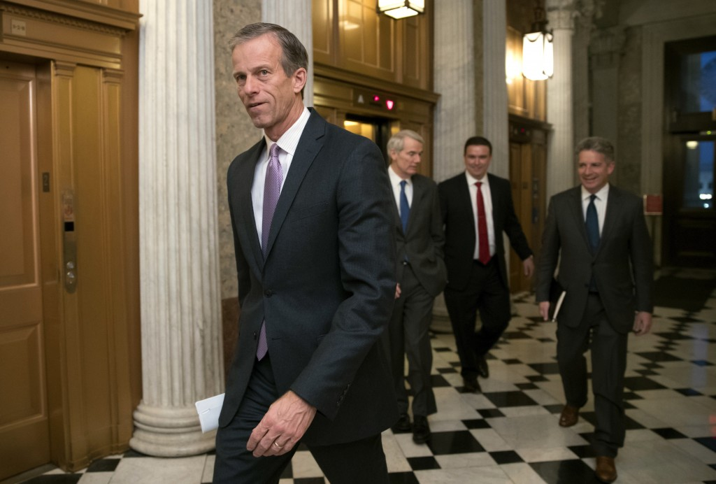 FILE - In this Dec. 18, 2017, file photo, Sen. John Thune, left, R-S.D., heads to a meeting at the Capitol in Washington. Congressional committees and