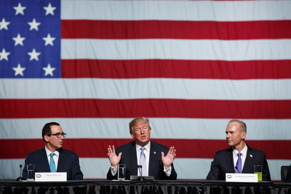 Treasury Secretary Steve Mnuchin, left, and Boeing CEO Dennis Muilenburg, right, listens as President Donald Trump speaks during a roundtable discussi