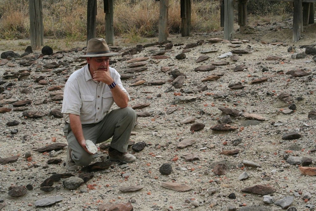 This undated photo provided by Jason Nichols via the Smithsonian's Human Origins Program shows Richard Potts with artifacts in the Olorgesailie Basin