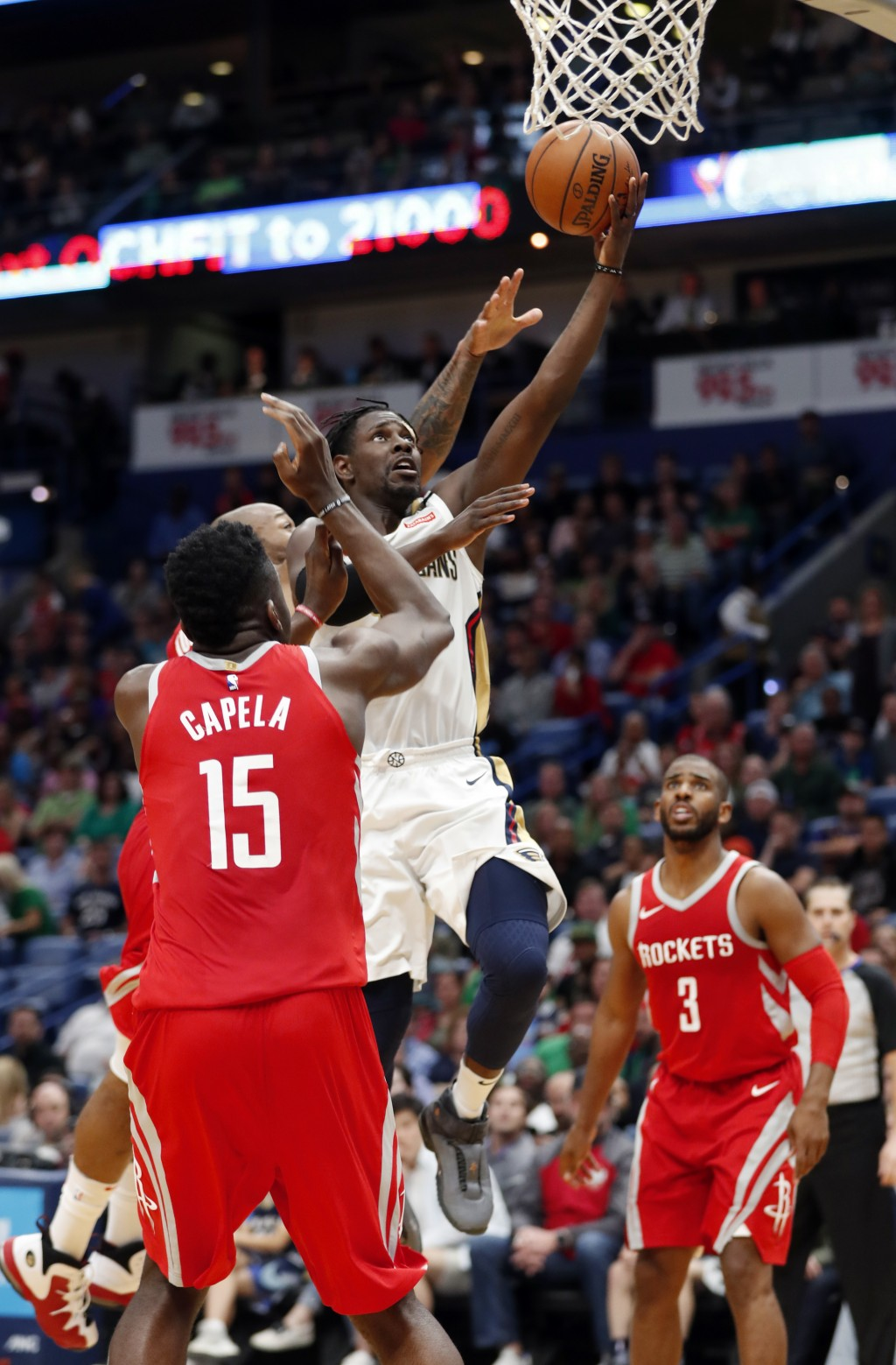 New Orleans Pelicans guard Jrue Holiday (11) goes to the basket in front Houston Rockets center Clint Capela (15) during the second half of an NBA bas...