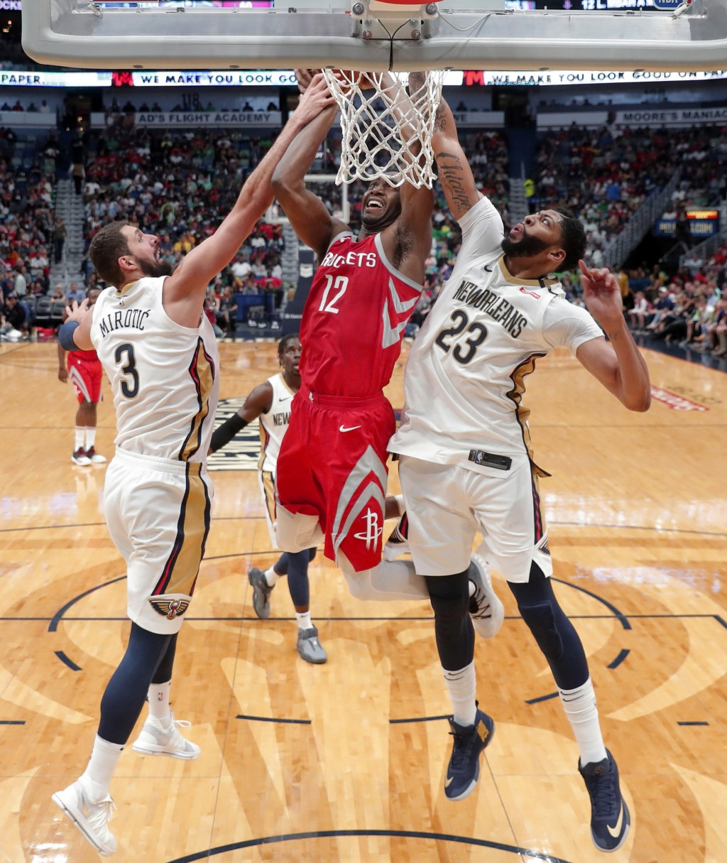 Houston Rockets forward Luc Mbah a Moute (12) is stopped by New Orleans Pelicans forwards Anthony Davis (23) and Nikola Mirotic (3) as he drives to th...