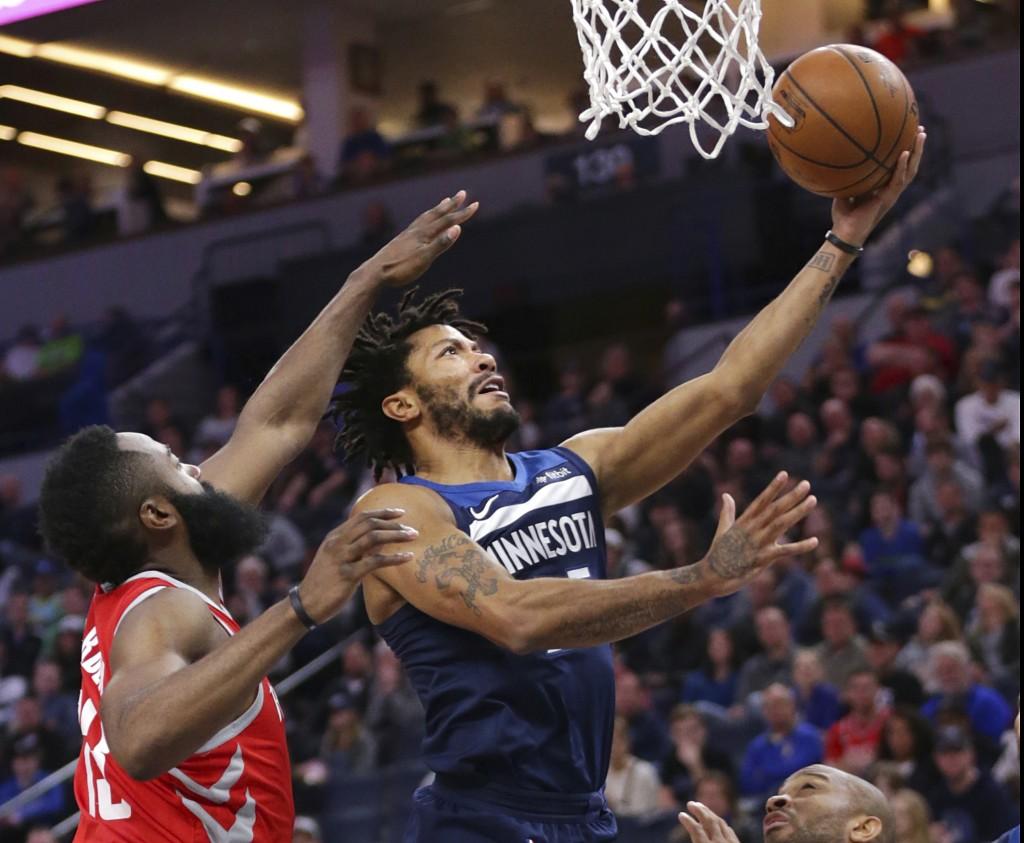 Minnesota Timberwolves Derrick Rose (25) shoots over Houston Rockets guard James Harden (13) in the first quarter of an NBA basketball game Sunday, Ma...