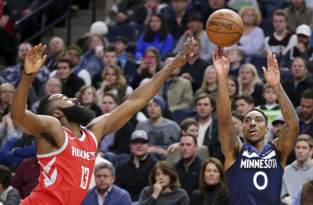 Minnesota Timberwolves guard Jeff Teague (0) shoots over Houston Rockets guard James Harden (13) in the first quarter of an NBA basketball game Sunday...