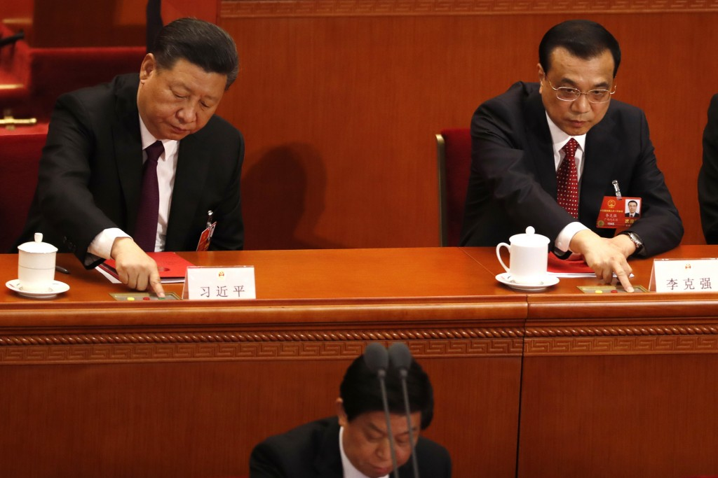 Chinese President Xi Jinping, left, and Premier Li Keqiang, right, press the green buttons to show their approval of government work reports and propo...