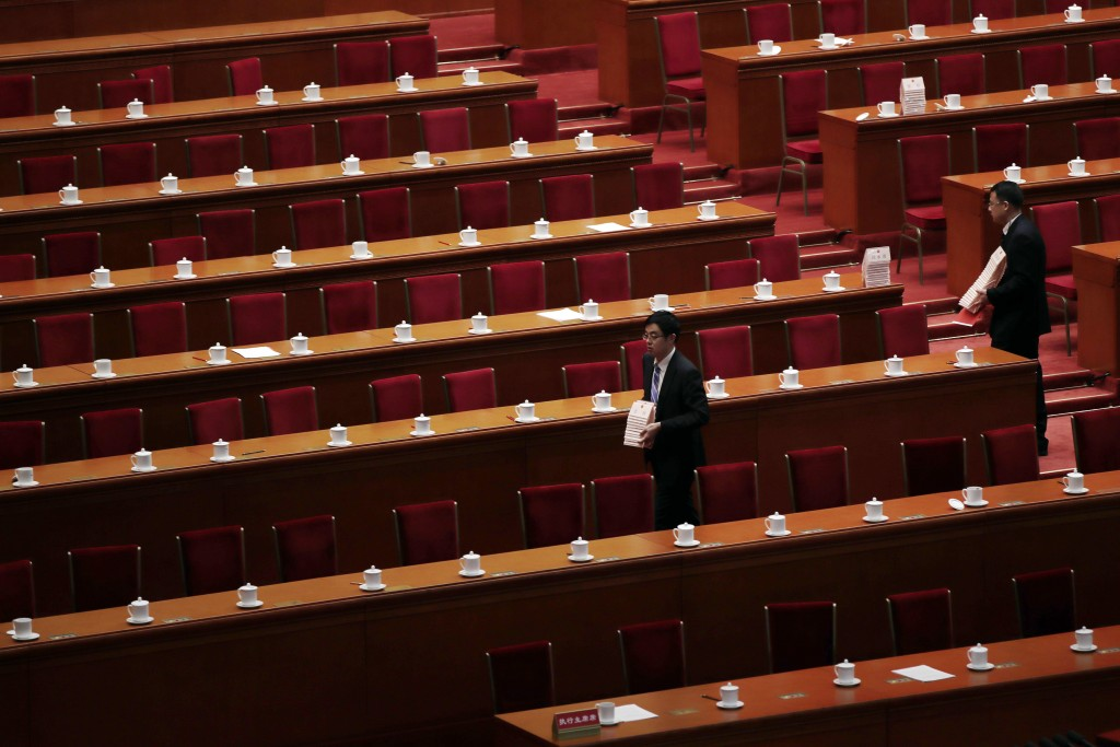 Staff members collect the delegates' name tags after the closing session of the annual National People's Congress (NPC) at the Great Hall of the Peopl...