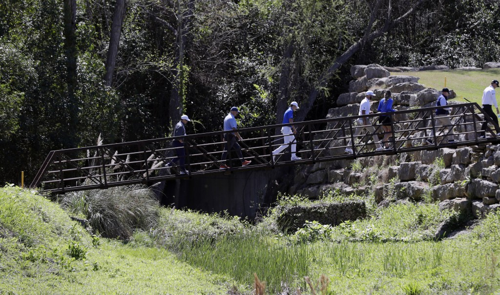 Jordan Spieth, center, and Dustin Johnson, center right, cross a pedestrian bridge on the fourth hole during a practice round at the Dell Technologies...