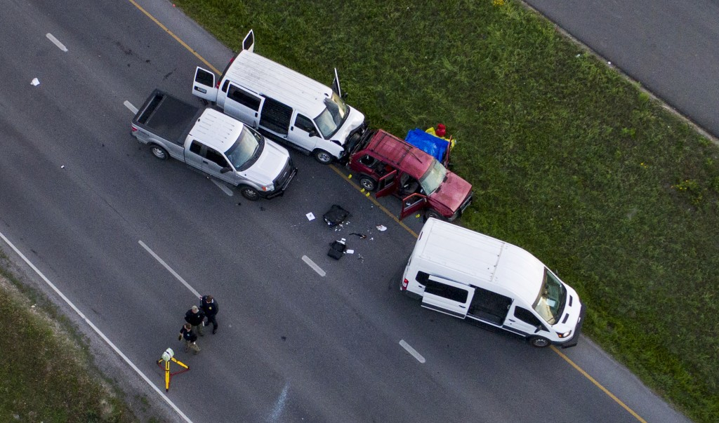 Officials investigate near a vehicle, center, where a suspect in the deadly bombings that terrorized Austin blew himself up as authorities closed in o...