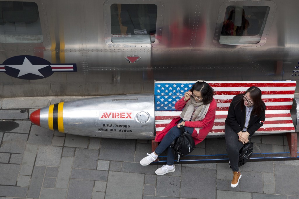 In this Friday, March 23, 2018, file photo, Chinese women sit on a bench with a U.S. flag theme outside an apparel store in Beijing. China announced o...