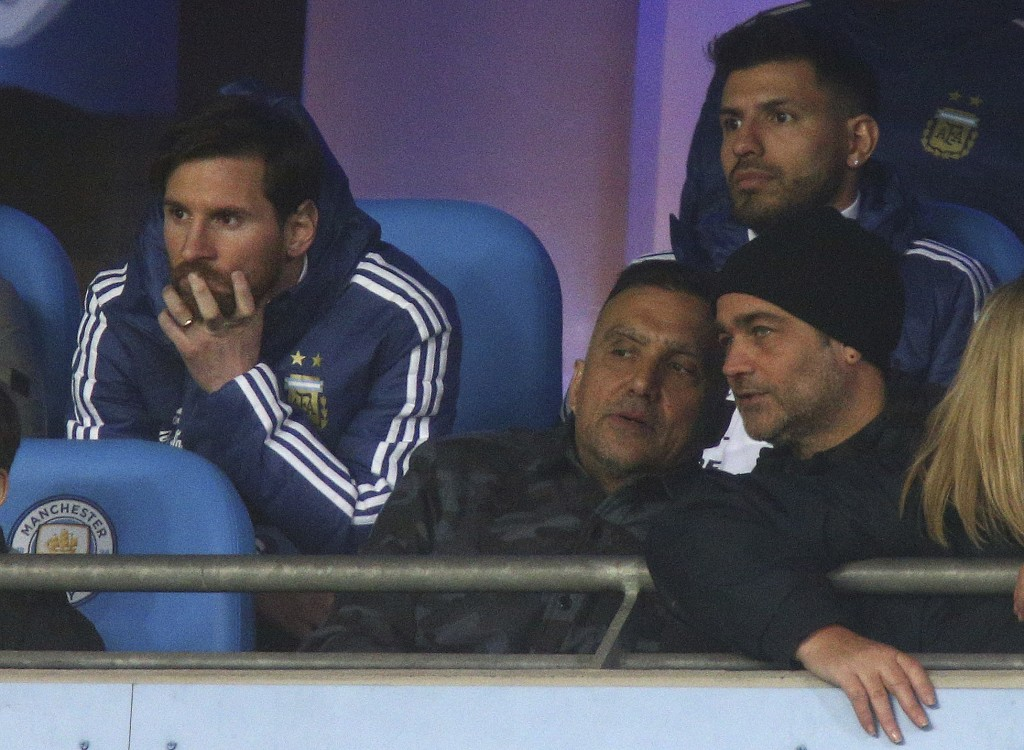 Argentina's Lionel Messi, left, and Sergio Aguero, top right, sit on the bench before the international friendly soccer match between Argentina and It...
