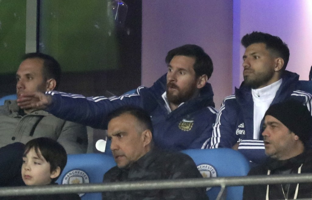 Lionel Messi, centre, and Sergio Aguero are seen in the stands during the international friendly soccer match between Argentina and Italy at the Etiha...
