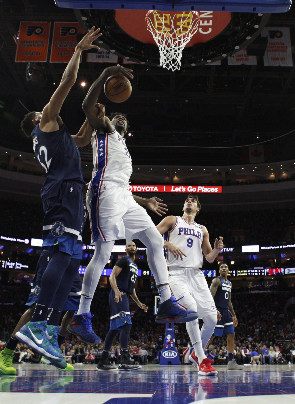 Philadelphia 76ers' Joel Embiid, front right, pulls down the rebound as he is fouled by Minnesota Timberwolves' Karl-Anthony Towns, left, during the f...