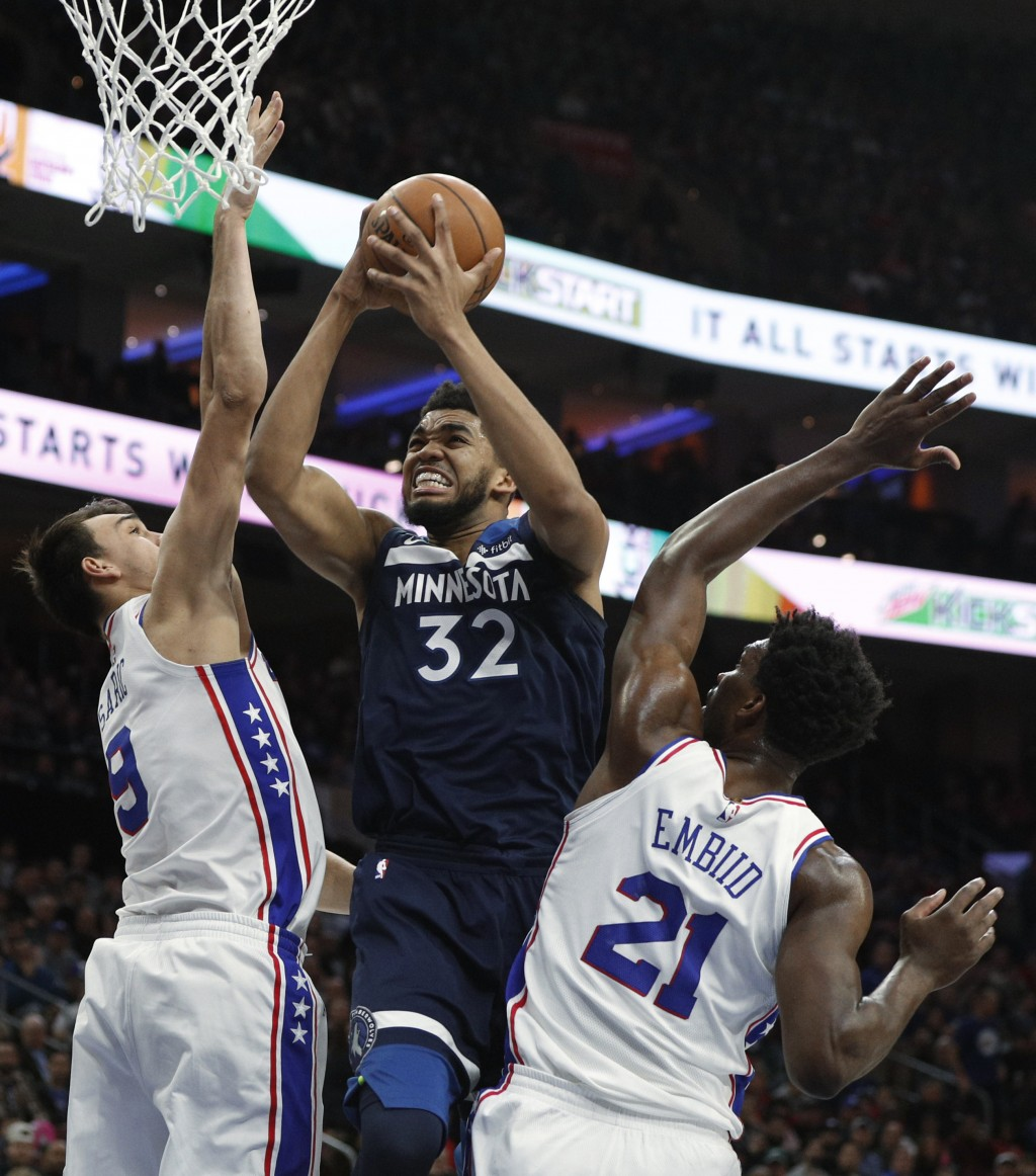 Minnesota Timberwolves' Karl-Anthony Towns, center, goes up for a shot between Philadelphia 76ers' Dario Saric, left, and Joel Embiid, right, during t...
