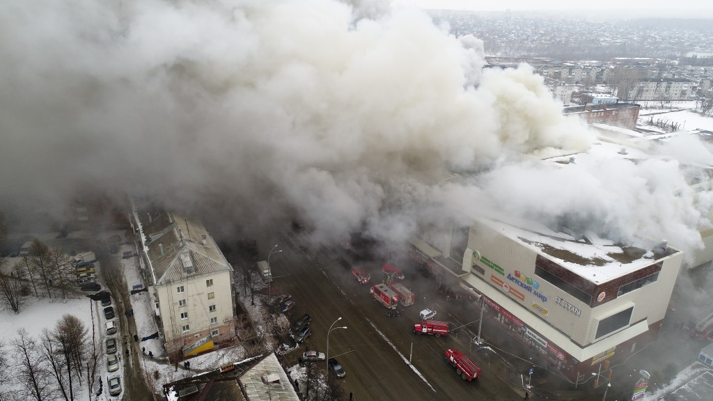 In this Russian Emergency Situations Ministry photo, on Sunday, March 25, 2018, smoke rises above a multi-story shopping center in the Siberian city o