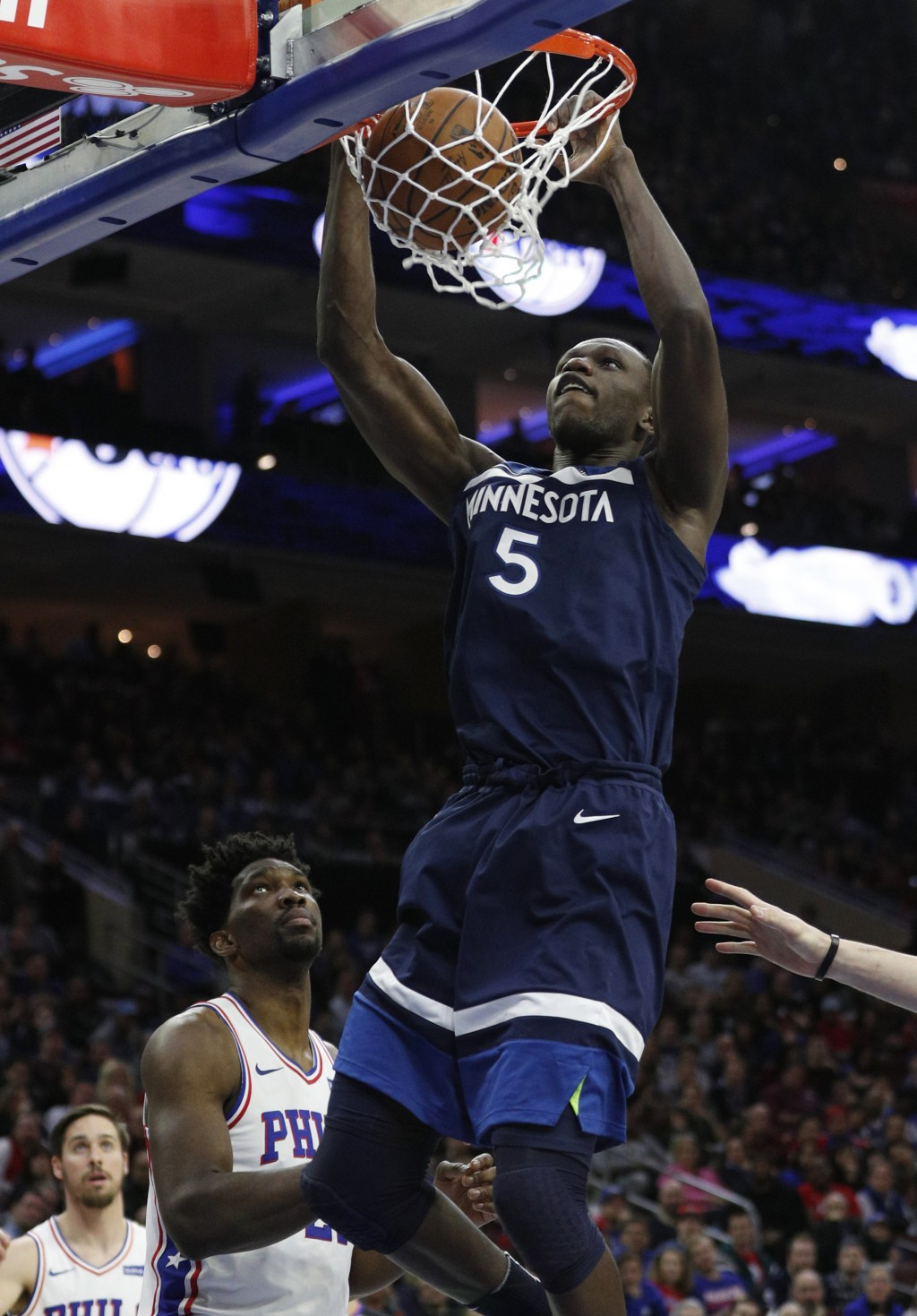 Minnesota Timberwolves' Gorgui Dieng dunks as Philadelphia 76ers' Joel Embiid watches during the first half of an NBA basketball game Saturday, March ...