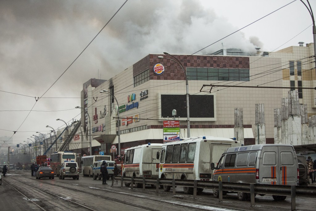 Smoke rises above a multi-story shopping center in the Siberian city of Kemerovo, about 3,000 kilometers (1,900 miles) east of Moscow, Russia, on Sund...