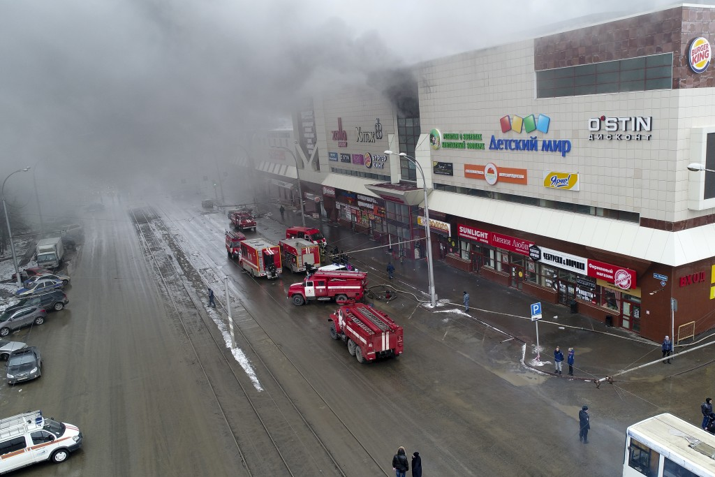 In this Russian Emergency Situations Ministry photo on Sunday, March 25, 2018, smoke rises above a multi-story shopping center in the Siberian city of