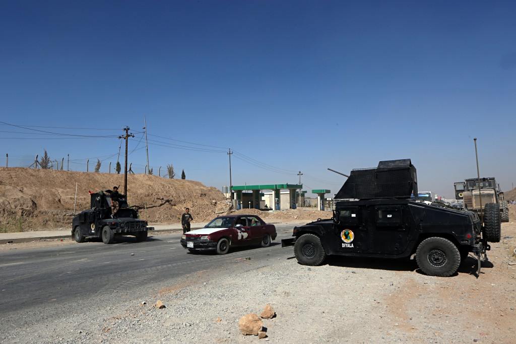 FILE - In this Oct. 17, 2017 file photo, federal security forces and local police man a checkpoint at the northern entrance to Kirkuk, Iraq. Islamic S...