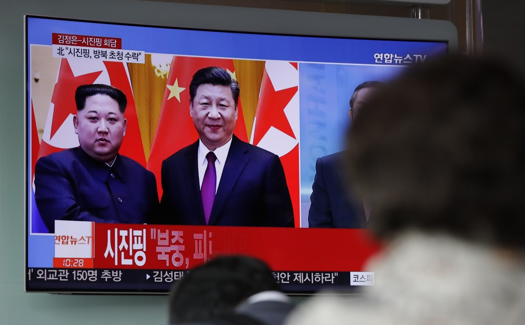 People watch a news program on TV reporting about the meeting between North Korean leader Kim Jong Un and Chinese President Xi Jinping at the Seoul Ra...