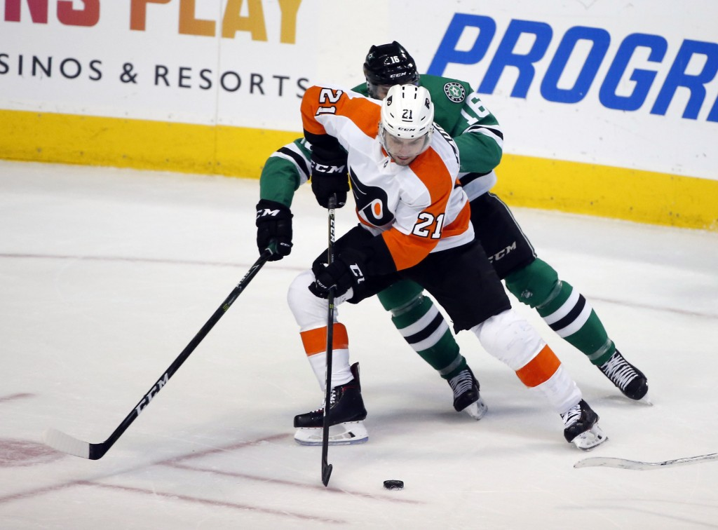 Philadelphia Flyers center Scott Laughton (21) fights for possession of the puck as he is defended by Dallas Stars center Jason Dickinson (16) during ...