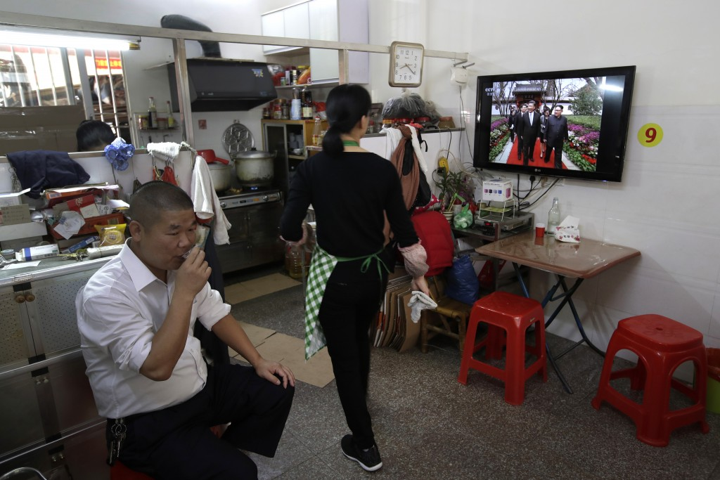 A food vendor walks by  a TV which shows CCTV broadcasting a morning news of North Korean leader Kim Jong Un and Chinese President Xi Jinping, at a re...