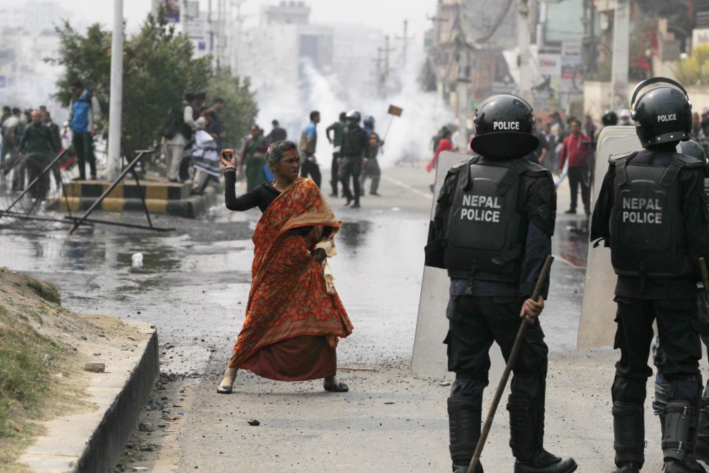 In this Wednesday, March 28, 2018, file photo, a Nepalese woman hurls a stone at policemen during a protest in Kathmandu, Nepal. Police set water cano...