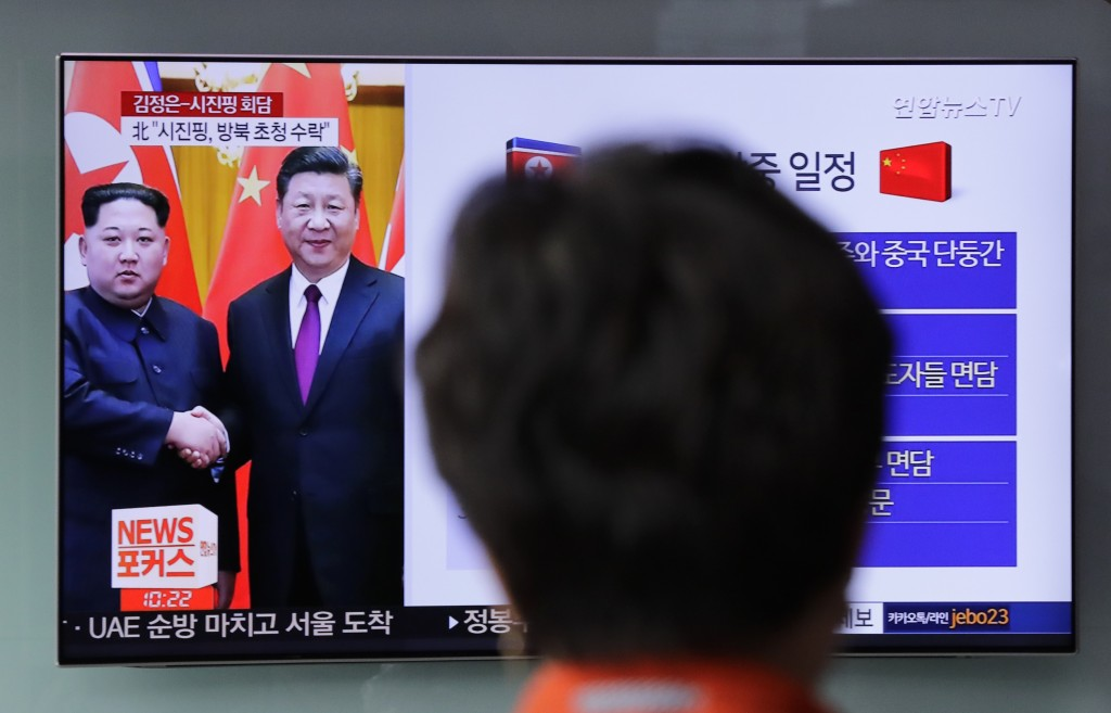 A woman watches a news program on TV reporting about the meeting between North Korean leader Kim Jong Un and Chinese President Xi Jinping at the Seoul...