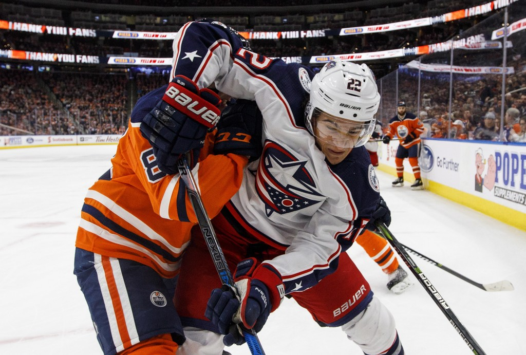 Columbus Blue Jackets' Sonny Milano (22) and Edmonton Oilers' Matthew Benning (83) battle for the puck during first period NHL hockey action in Edmont...