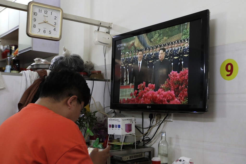A Chinese man browses his mobile phone near a TV which shows CCTV reporting a morning news of North Korean leader Kim Jong Un and Chinese President Xi...